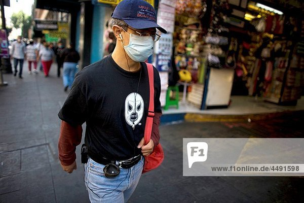 A man wearing a Mexican wrestling t-shirt wears a mask as a precaution against swine flu walks in Mexico City´s main Zocalo square  April 30  2009