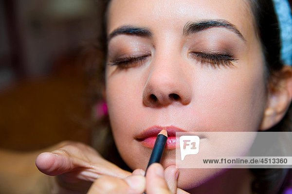 Make up artist applying lips liner on a woman´s lips