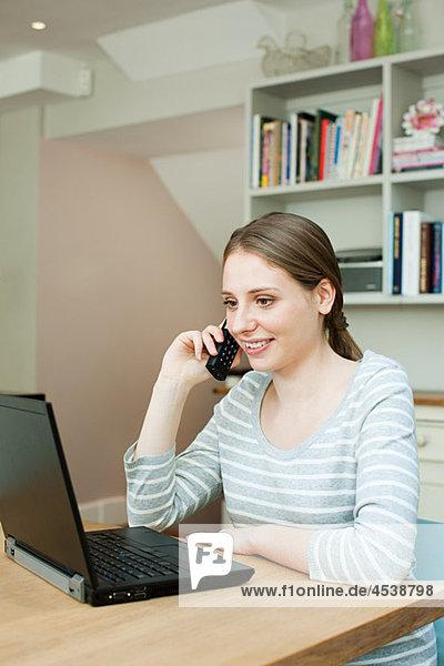 Junge Frau mit Laptop und Telefon