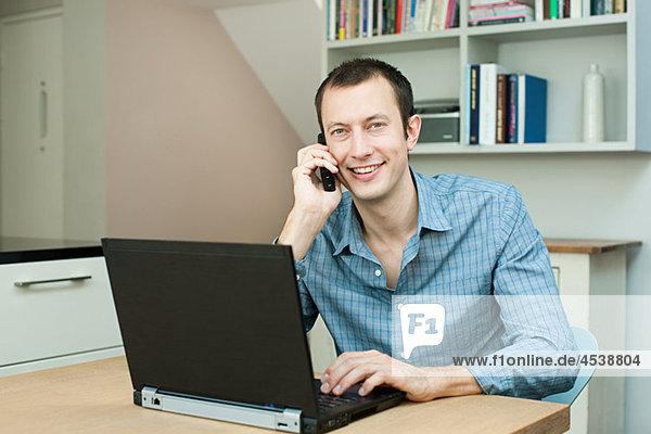 Junger Mann mit Laptop und Telefon
