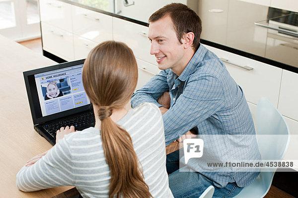 Junges Paar sucht Versicherung auf dem Laptop
