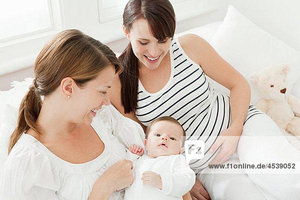 Mutter mit Mädchen und schwangerer Freundin