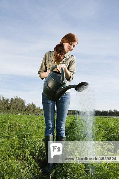 Frau beim Gießen von Getreide auf dem Feld mit Gießkanne