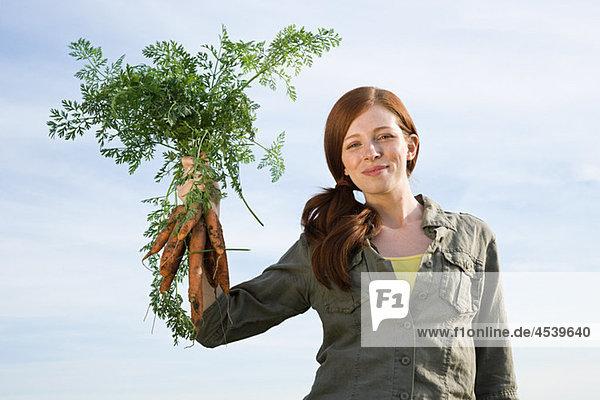 Junge Frau mit frisch gepflückten Karotten Junge Frau mit frisch gepflückten Karotten