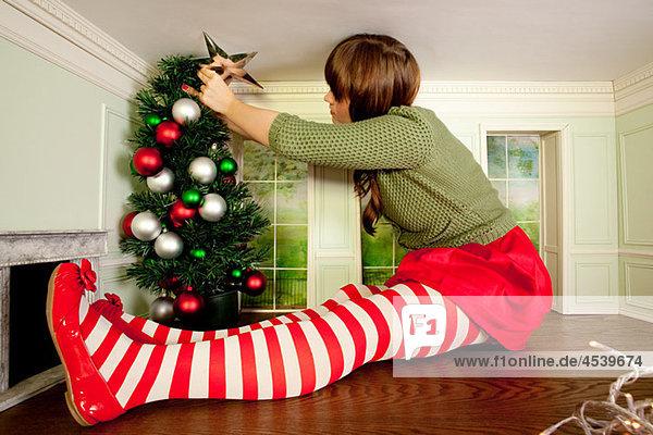 Junge Frau in kleinem Raum schmückt Weihnachtsbaum