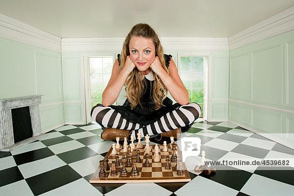 Junge Frau in kleinem Raum mit Schachspiel