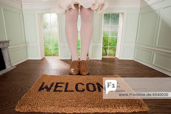 Beine einer Frau und Begrüßungsmatte im kleinen Zimmer
