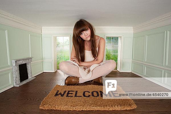 Junge Frau im kleinen Zimmer mit Begrüßungsmatte