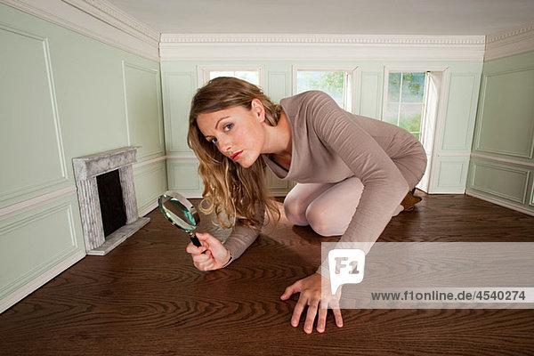 Junge Frau in kleinem Raum mit Lupe