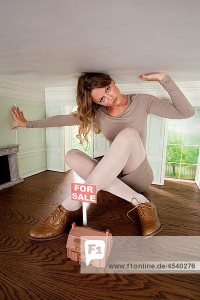 Junge Frau in kleinem Haus mit Hausmodell zu verkaufen