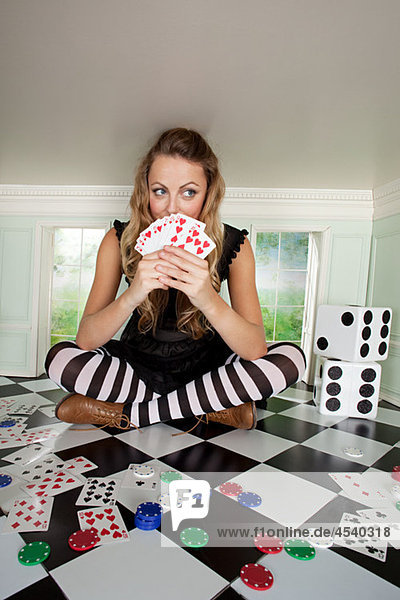 Young woman in small room with playing cards and dice
