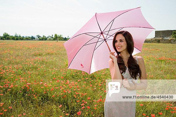 Junge Frau im Mohnfeld mit rosa Sonnenschirm