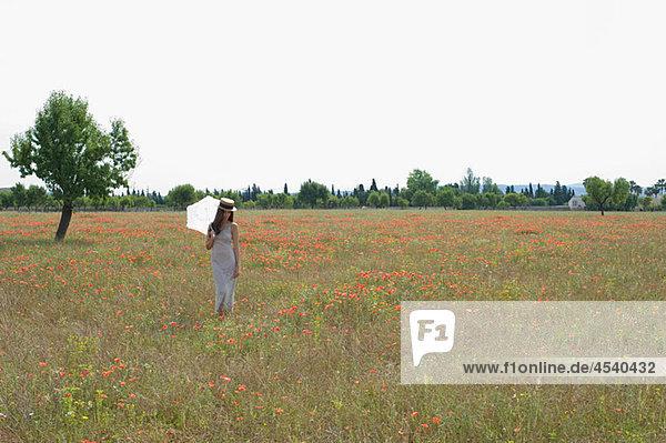 Junge Frau stehend Poppy Feld mit weißen parasol