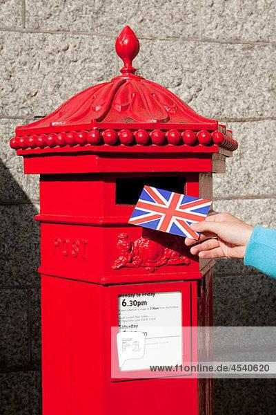 Person  die Postkarte in den Briefkasten legt  London