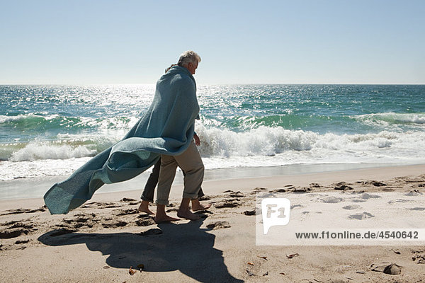 Mature couple walking on beach wrapped in blanket
