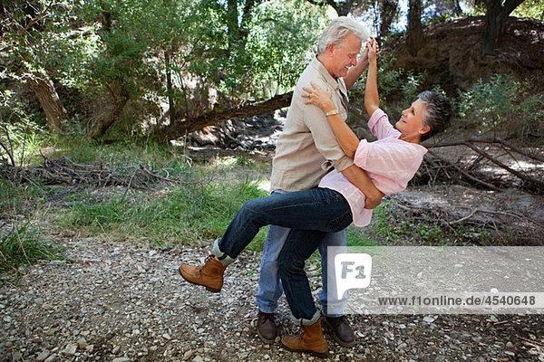 Reife Paare tanzen im Wald