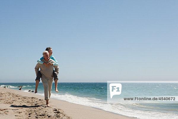 Huckepack-Paar am Strand