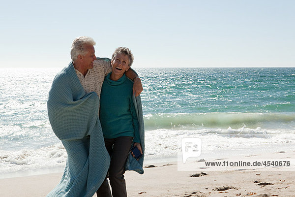 Mature couple on beach wrapped in blanket