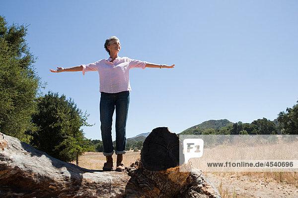 Seniorin auf einem Baumstamm stehend mit offenen Armen