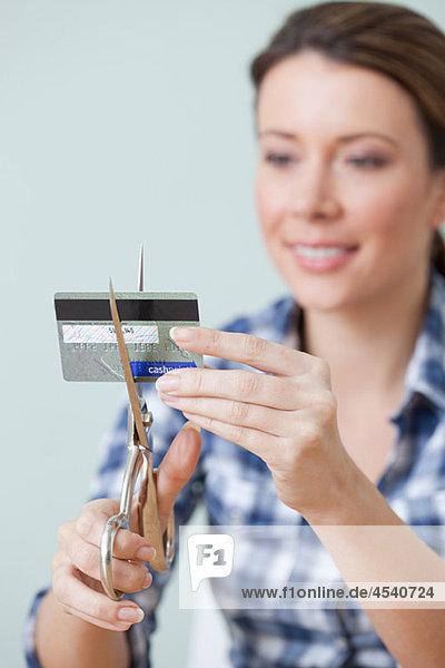 Junge Frau schneidet Kreditkarte