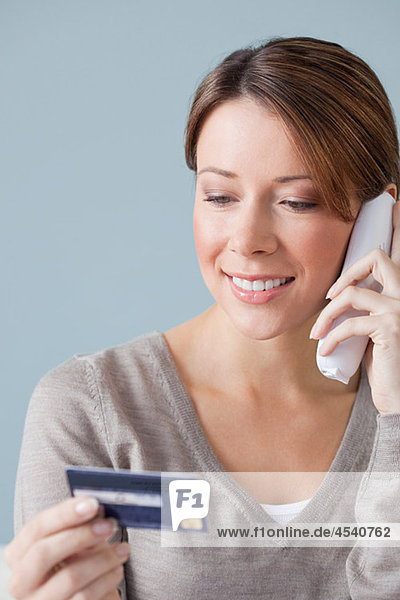 Junge Frau am Telefon mit Kreditkarte