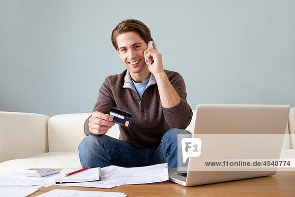 Junger Mann mit Kreditkarte mit Laptop