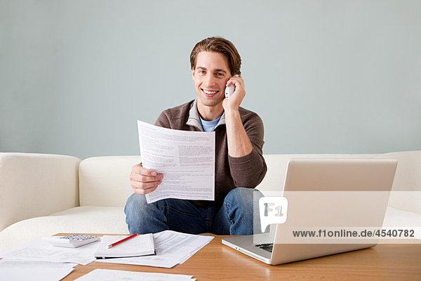 Junger Mann mit Papierkram am Laptop