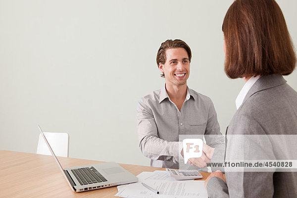 Junger Mann beim Händeschütteln mit Finanzberater