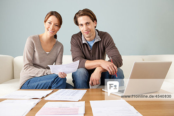 Young couple using computer and doing paperwork