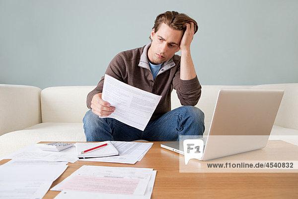 Besorgter junger Mann mit Papierkram am Laptop