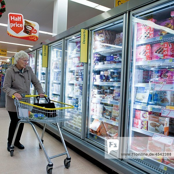 A woman with a trolley shopping for food in a branch of the Co-op supermarket  UK