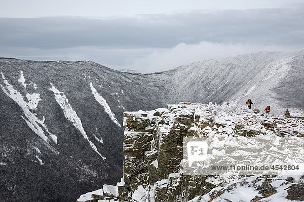 Pemigewasset Wilderness - Backcountry campers travel along the Bondcliff Trail on the summit of Bondcliff Mountain during the winter months in the White Mountains  New Hampshire USA Hellgate Ravine is in the background