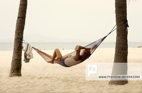 people resting on a hammock Cua Dai beach Hoi An  Vietnam  Asia