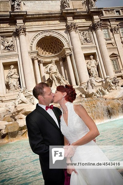 Wedding couple kissing in front of Fontana di Trevi Rome Italy