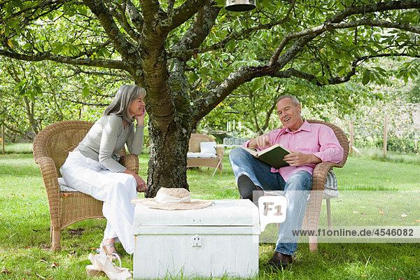 Mature couple outdoors  man reading book