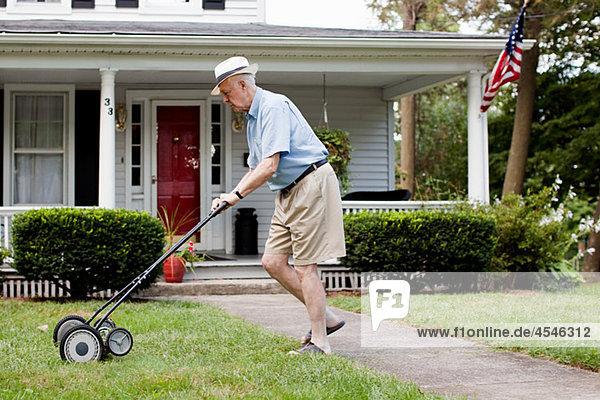 Älterer Mann mäht seinen Rasen.