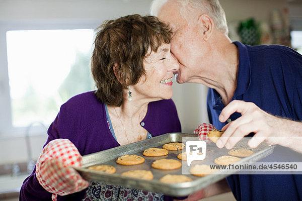 Seniorenpaar beim Küssen mit selbstgebackenen Keksen