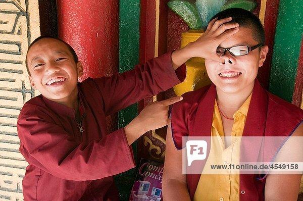 joking young Tibetan-Sherpa monks having fun at a monastery at Bodhnath in Kathmandu  Nepal