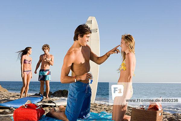 eincremen verteilen Mann Freundin Creme Salbe Lotion jung auftragen Sonne