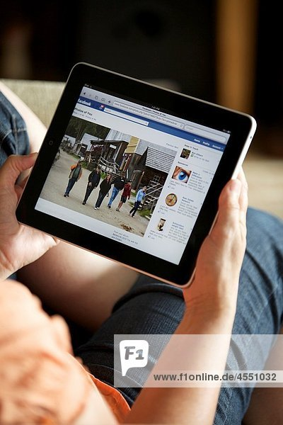 Close up of a woman hand holding an iPad checking her Facebook page