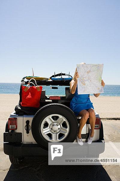 Junge Frau sitzt auf dem Fahrzeug und schaut auf die Karte.