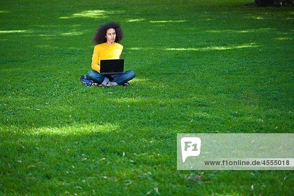 Junger Mann mit Afro Haar sitzen auf Gras mit laptop