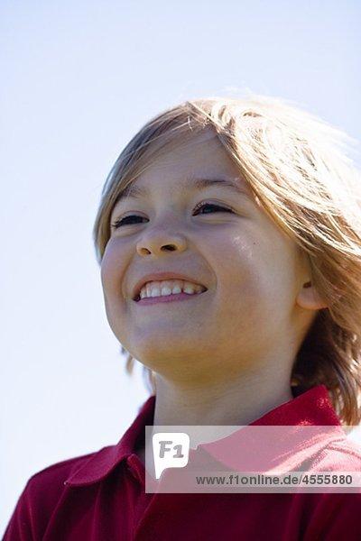 Porträt von lächelnder Junge in hellem Sonnenlicht