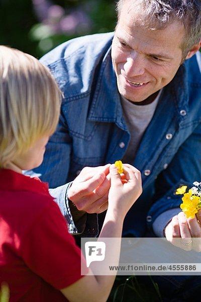Vater und Sohn mit Blumen in hellem Sonnenlicht