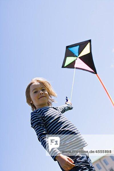 Porträt von Boy flying Kite in hellem Sonnenlicht  gegen Wolkenloser Himmel