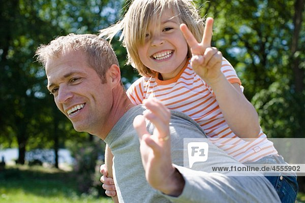 Piggyback portrait of father and son in bright sunlight