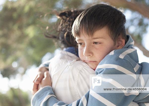 Junge umarmende Mutter