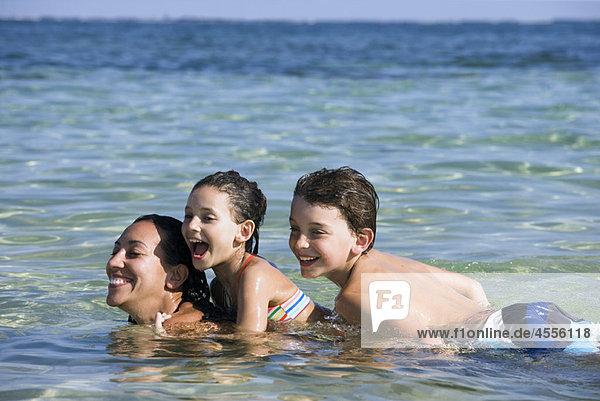 Mutter + 2 Kinder auf dem Rücken im Wasser
