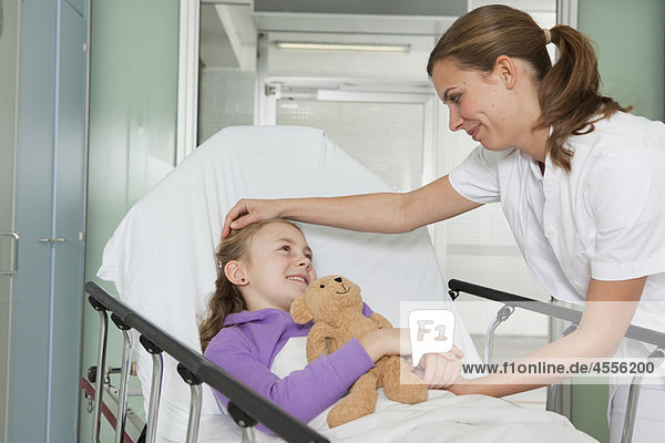 Krankenschwester streichelt krankes Mädchen