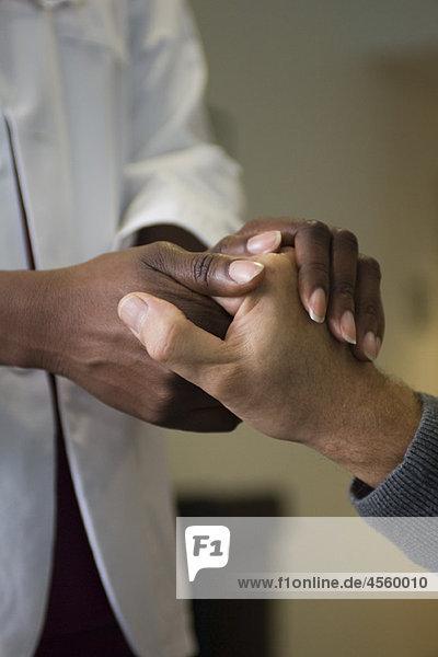Arzt hält die Hand des Patienten